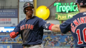 Rafael Devers #11 of the Boston Red Sox is congratulated by Andrew Benintendi #16 after scoring in the 11th inning of a baseball game against the Tampa Bay Rays at Tropicana Field on April 21, 2019 in St. Petersburg, Florida.