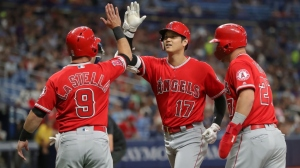 Shohei Ohtani #17 of the Los Angeles Angels, center, is congratulated on his three-run home run by Tommy La Stella #9 and Mike Trout #27 in the first inning of a baseball game at Tropicana Field on June 13, 2019 in St. Petersburg, Florida.