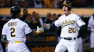 Mark Canha #20 celebrates scoring with Khris Davis #2 of the Oakland Athletics during the seventh inning against the Kansas City Royals at Ring Central Coliseum on September 17, 2019 in Oakland, California.